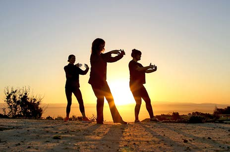 3 people practicing tai chi outdoors.