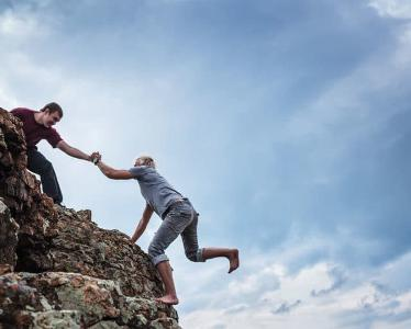 Man helping another man scale a rock.