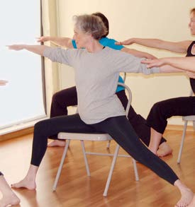 a woman performing yoga on a chair.