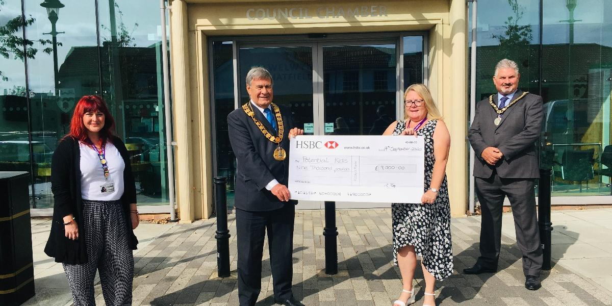 Mayor presenting fundraising cheque to Potential Kids