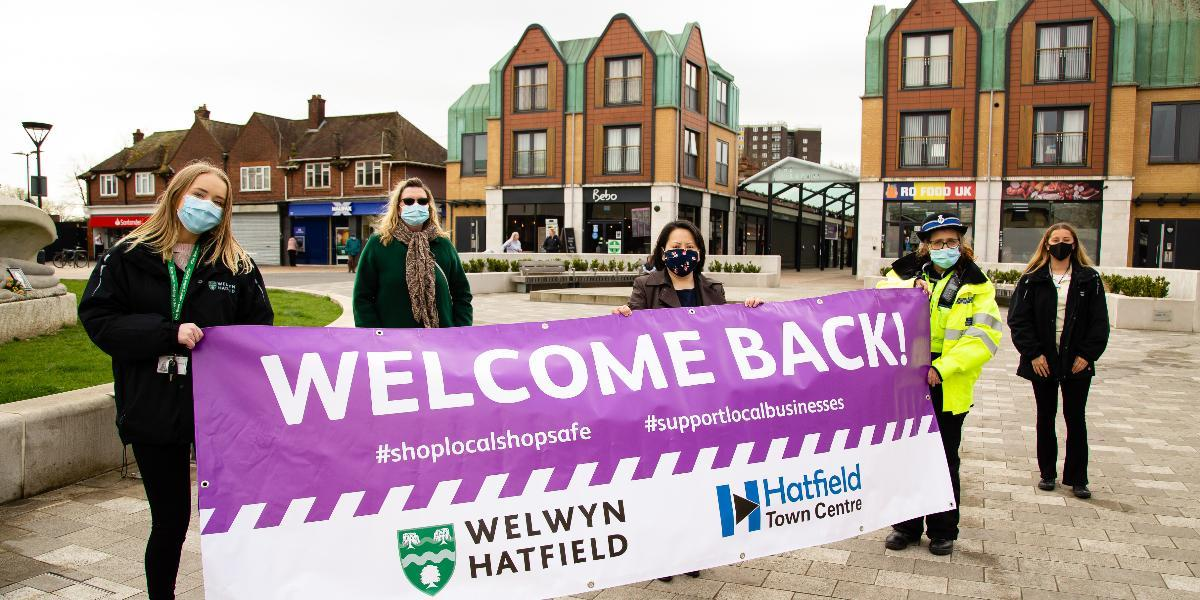 Council officers hold a welcome back banner in Hatfield town centre